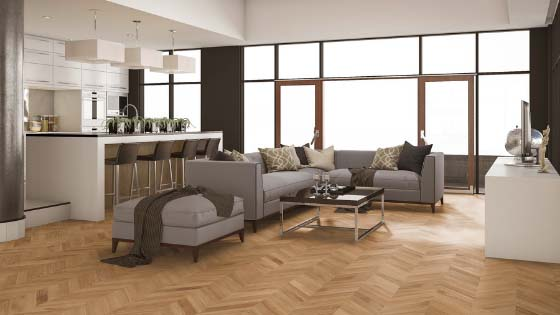 Kitchen island, grey couch, and coffee table on a blond oak floor in a chevron design