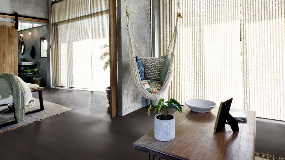 Sun shining into a room with a hammock chair, a coffee table, a bed and a rug on an engineered hardwoodwood floor.