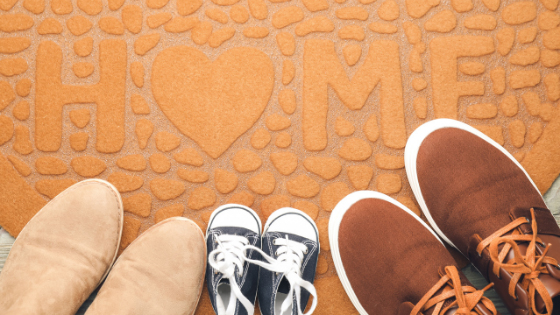 Two pairs of adult shoes and a pair of baby shoes on a yellow floor mat. Home is written on the mat
