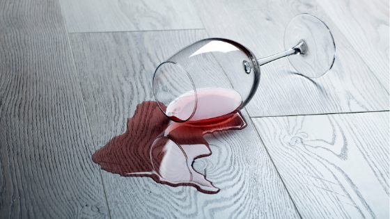 Red wine and a tipped over wine glass on a wood floor.